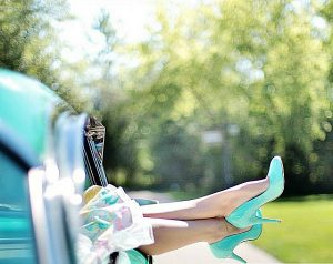 view of old teal car and teal heels hanging out window