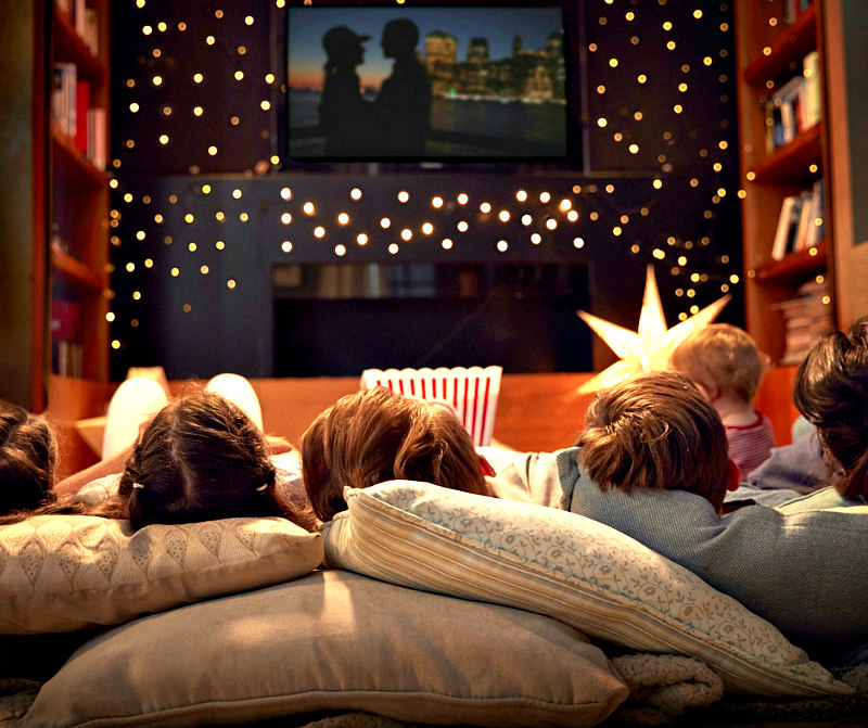 create a fabulously cozy family movie night that memories are made of - family shown on pillows watching movie