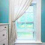 view of best way to clean blinds - blue room with white curtains and blinds