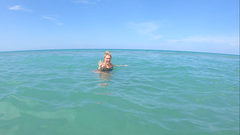 view of girl in Jensen Beach water in Hutchinson Island Florida ocean for best East Coast beaches