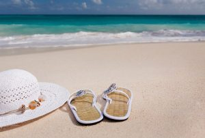 close up view of beach sand, ocean, beach hat and sandals - best spring break destinations