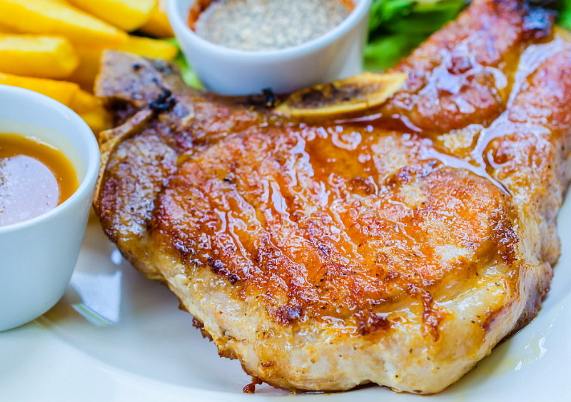 close up of low carb pork chop recipes - pork chop on plate with sauce and fries