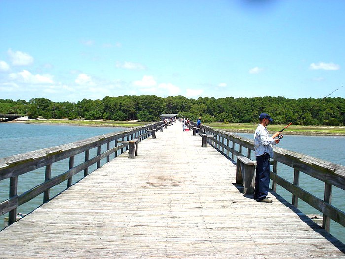 Long wooden Hunting Island Pier with several people fishing on the sides.