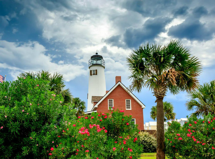 St George Lighthouse and Museum behind palm tree and colorful blooming bushes - best islands to visit.