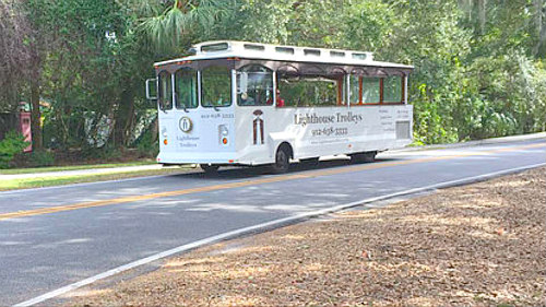 St. Simons Island Georgia's Lighthouse Trolley on two-laned road with trees in backdrop.