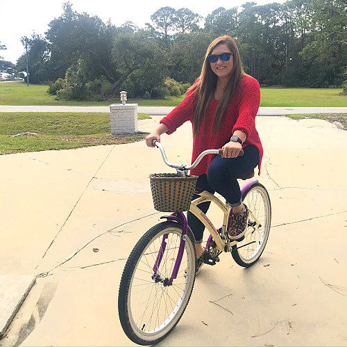 girl in red shirt and jeans sitting on pink bike in driveway of Jekyll Island rental house