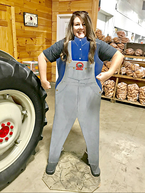 women posing behind wooden overalls cutout inside old-fashioned general store