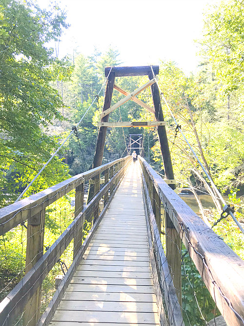 swinging suspension bridge with person in distance walking on it