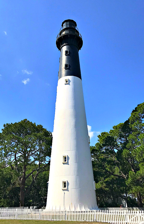 Black and white striped Hunting Island State Park Lighthouse with white picket fence and green trees surrounding it.