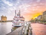 Savannah Georgia Riverboat Cruise ship on dock with River Street in background at sunset