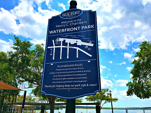 blue sign at Beaufort SC Waterfront Park with playground rules and River and trees in background