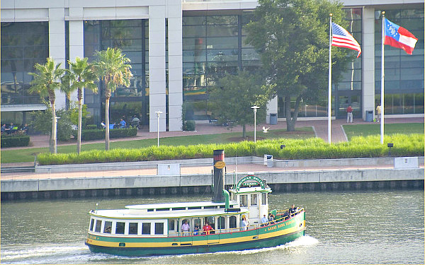 Savannah Belles Ferry in Savannah River and background of Hutchinson Island Convention Center and flags out front