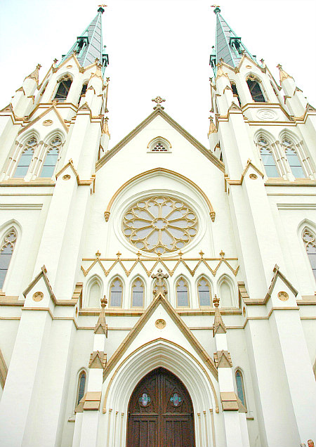 white and gold Cathedral Basilica of St. John the Baptist building with dark brown gothic door