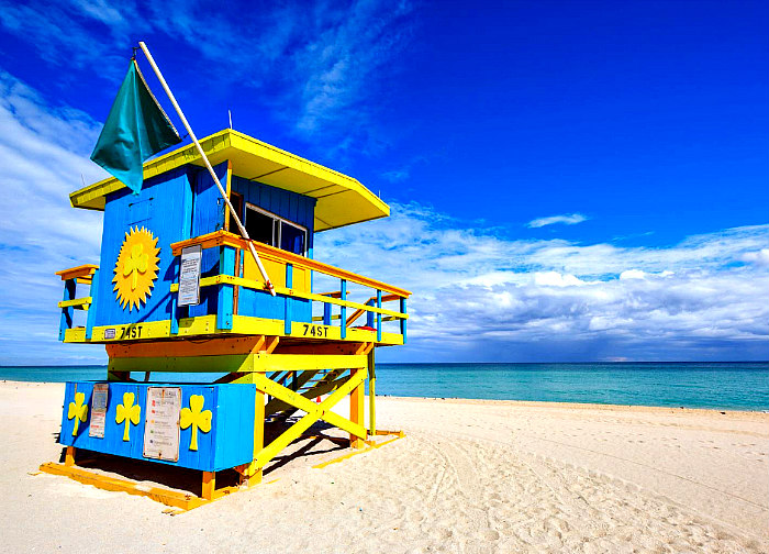 Bright blue and yellow wooden lifeguard stand and flag on Miami Beach Florida sand with ocean and sky in background.