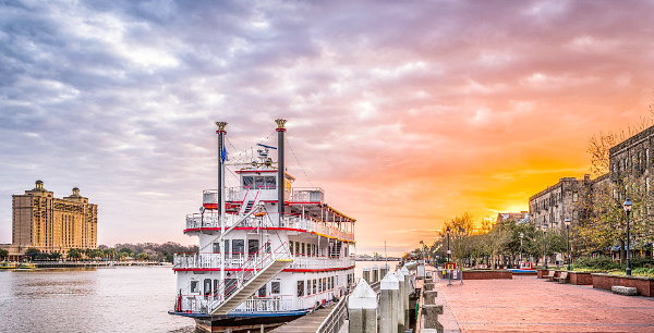 colorful sunset view of Hutchinson Island, Savannah Riverboat, and River Street