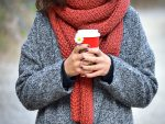 Fall Festival ready woman with dark hair, purple nails, gray sweater and orangey-red knit scarf.