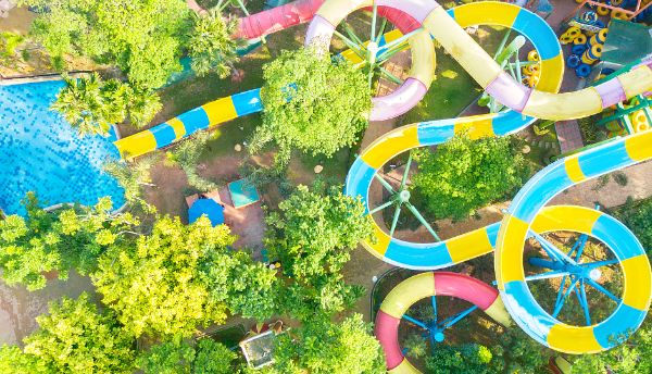 Rapids water park aerial view of colorful waterslides, blue pool, and trees.